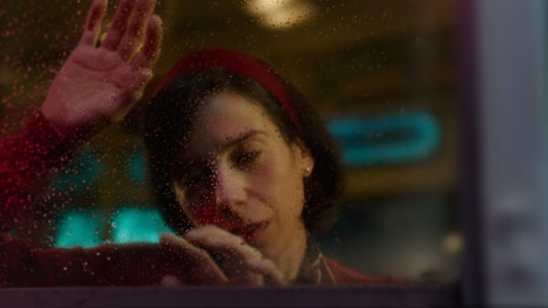 Elisa with her hand on glass