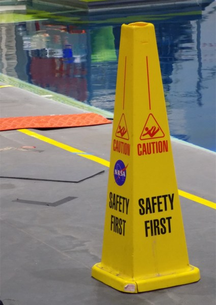 "A yellow cone which has the NASA logo on is, as well as a falling red man, and ""caution"" and ""safety first"" on the side, next to a pool."