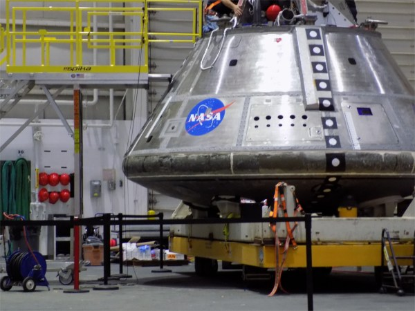 A giant rounded metal cone shaped tin can on a yellow platform. The can has a line of black squares with white dots in the middle, and a large NASA insignia