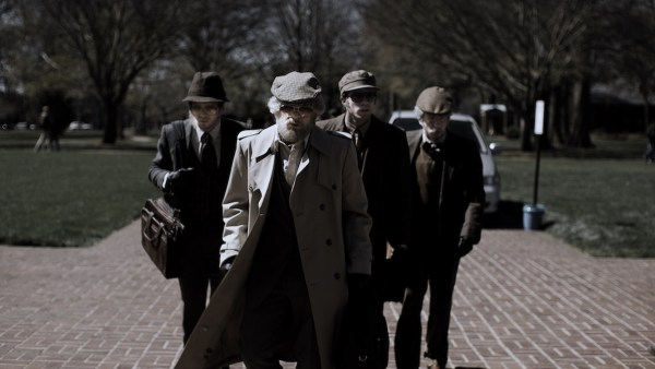 The four main characters wearing long coats and sunglasses, walking suspiciously towards the camera.