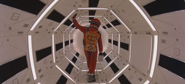 A figure in a spacesuit stands in a hallway