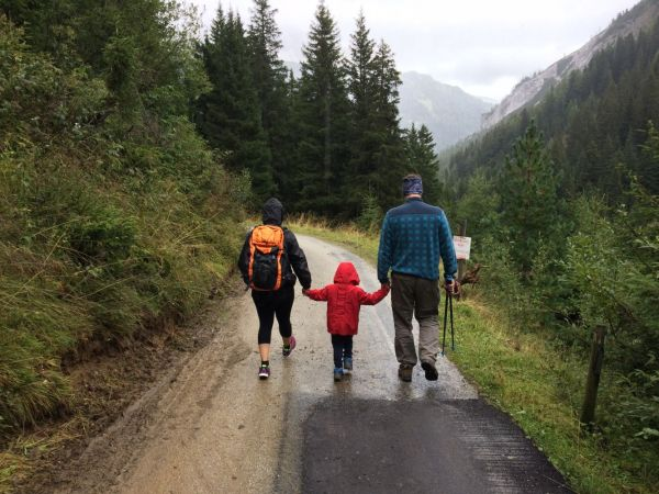 Two adults and a child on a forest path
