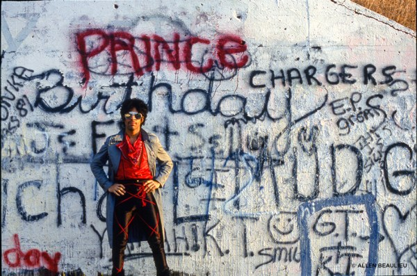 Prince posing against a graffitied wall