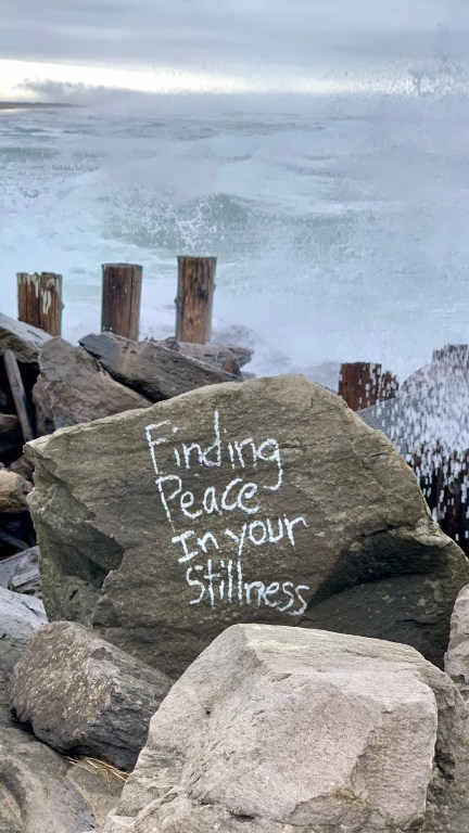 Finding peace in your stillness? A sneaker wave crashes over a boulder inscribed with this phrase at Fort Stevens State Park, January 2021.
