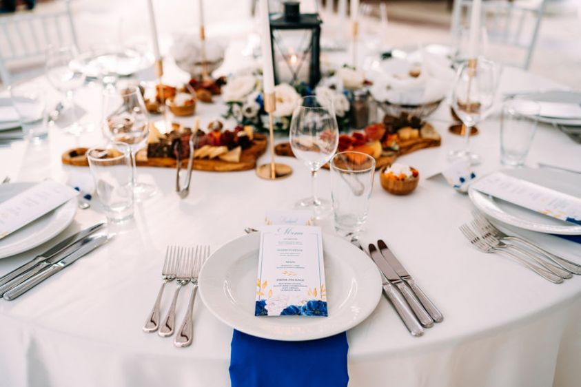 Wedding dinner table reception. White plate on the table, three forks on the left, three knives on the right. The wedding menu is in the plate