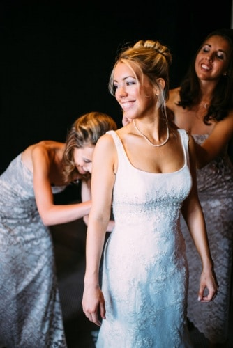 Bridesmaids applying the finishing touches to their brides dress