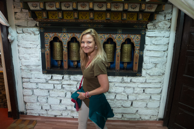 Shauna turning prayer wheels at a restaurant before lunch - I imagine praying for a good meal.