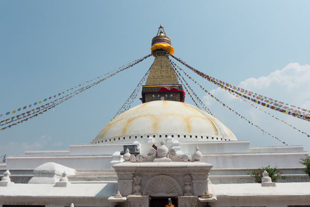 """The Buddhist stupa of Boudhanath dominates the skyline. The ancient Stupa is one of the largest in the world. The influx of large populations of refugees from Tibet has seen the construction of over 50 Tibetan Gompas (Monasteries) around Boudhanath. As of 1979, Boudhanath is a UNESCO World Heritage Site.  This stupa was featured in the movie """"Little Buddha""""."""