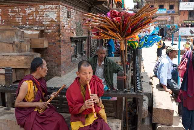 Buddhist monks trying out different flutes to find just the right pitch.