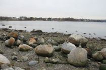Someone goes along stacking rocks along the shore