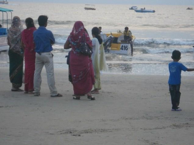 Colva. Muita gente, todos de roupa e entram assim na água.