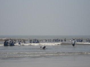 Turma da escola tomando banho de mar de uniforme