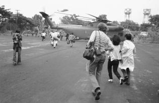 Americans and Vietnamese run for a U.S. Marine helicopter in Saigon during the evacuation of the city, April 29, 1975. (AP Photo)