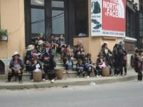 Minorias esperando a chegada de um ônibus de turistas