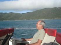 Carlos se segurando no barco chacoalhando e ventando. Ao fundo Fitzroy Island