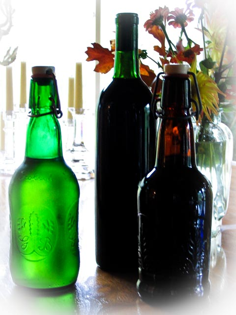 Grolsch bottles of carbonated beverages and a bottle of port setting on a table