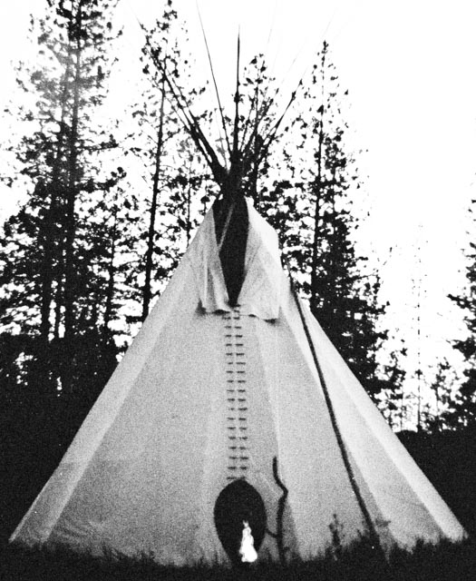 Ceremonial Lakota TiPi at twilight with ceremonial fire burning inside (high-contrast black and white photo)