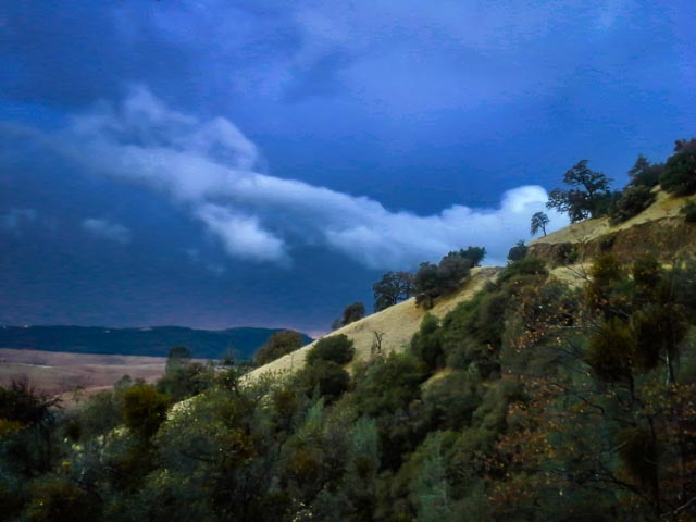 purple and white storm clouds over Lake Oroville (lake bed is visibile because it is low) and yellow and green foothills in foreground