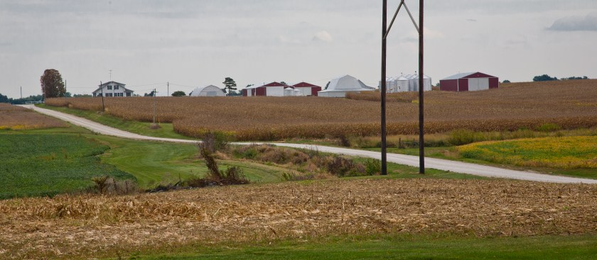 Midwestern farmscape with large, 1930s farm home, barns, bins, sheds, fields and dirt road