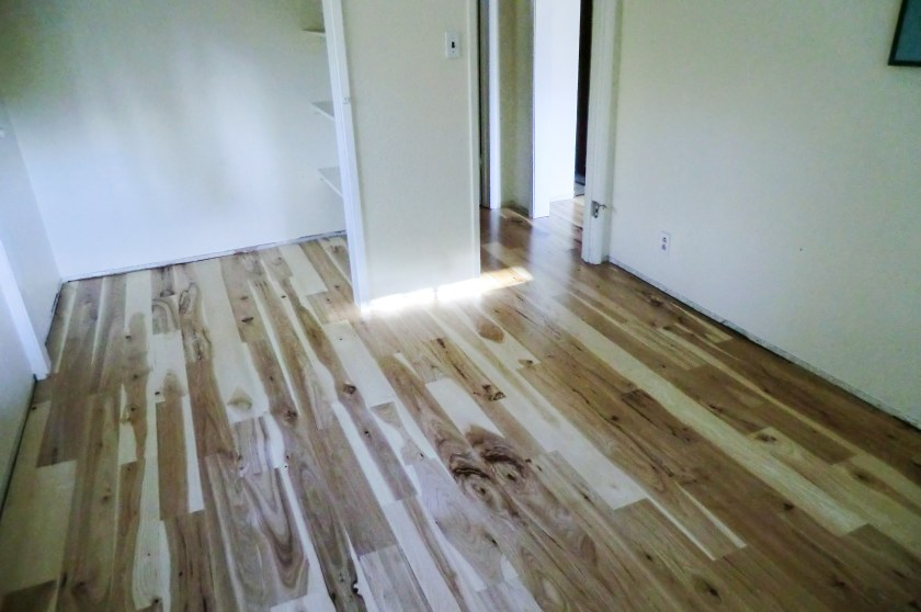 a new, hardwood plank hickory floor in a bedroom