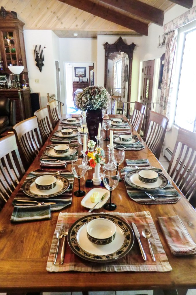 A long, eastern black-walnut table with 9 place settings.