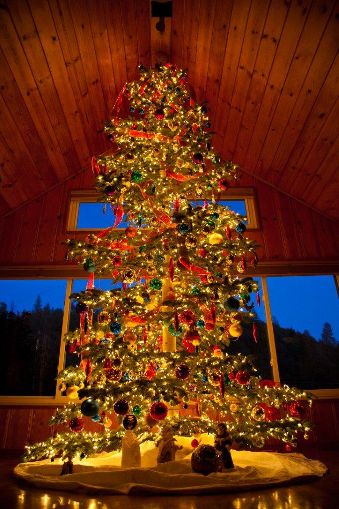 Picture of a lit, decorated Christmas tree in a house a night. Thousands of lights and hundreds of colorful and unusual ornaments. Stunning, with twilight mountains in background throug the windows