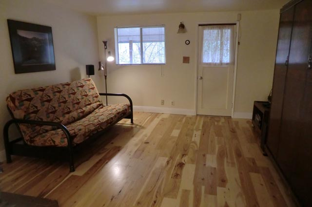 A living room with a futon, lit corner lamp, wall photo and new, hickory hardwood floor.