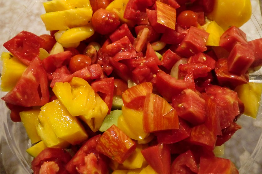 Juicy, bright red and yellow tomatoes diced in a bowl.