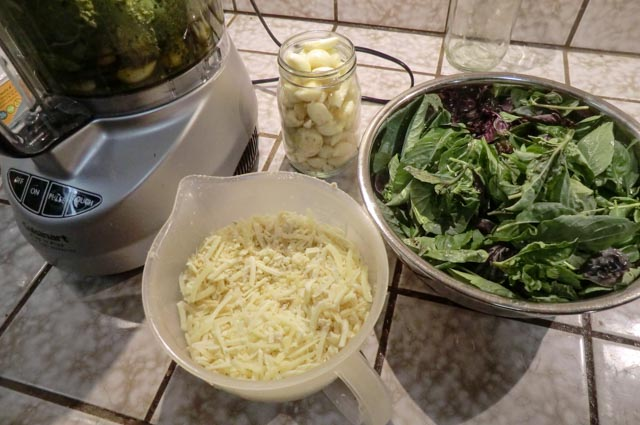 a food processor next to containers of grated cheese, garlic and basil