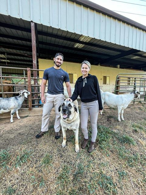 Two people with an Anatolian Shepherd Dog