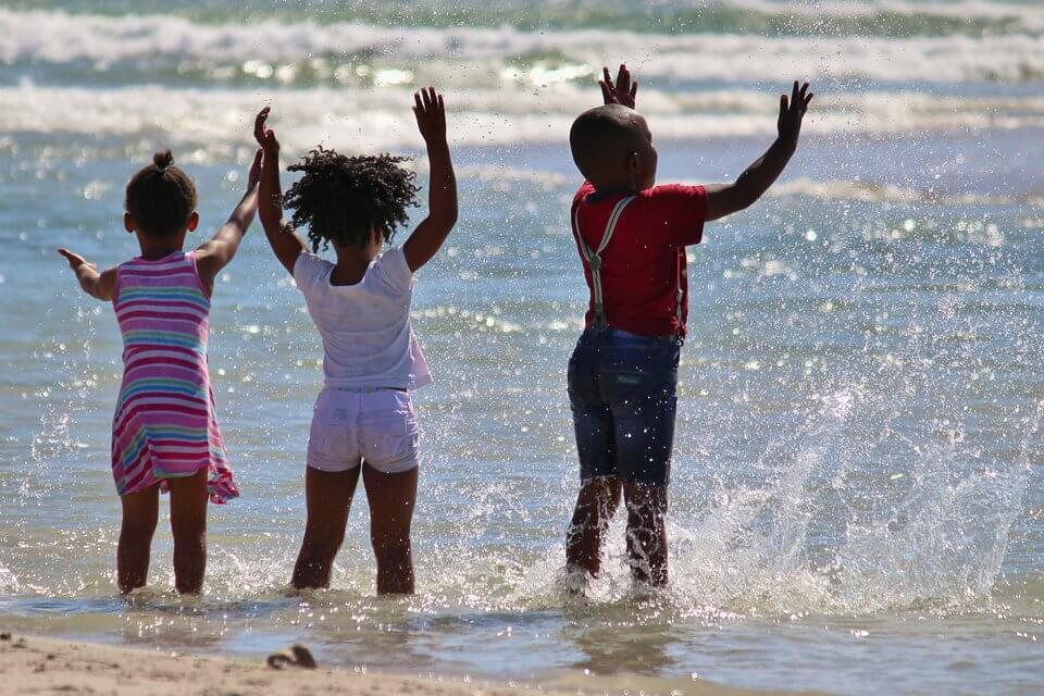 Three children splashing in the waves