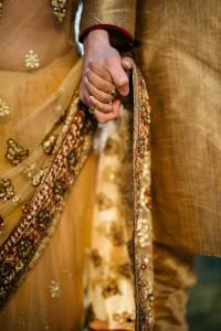 Indian couple wearing traditional dress and holding hands; cross-cultural marriage tips