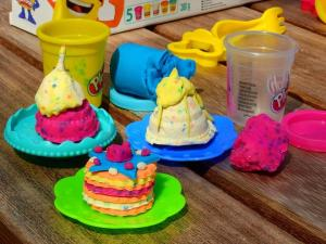 Colored play dough in the shape of cakes.
