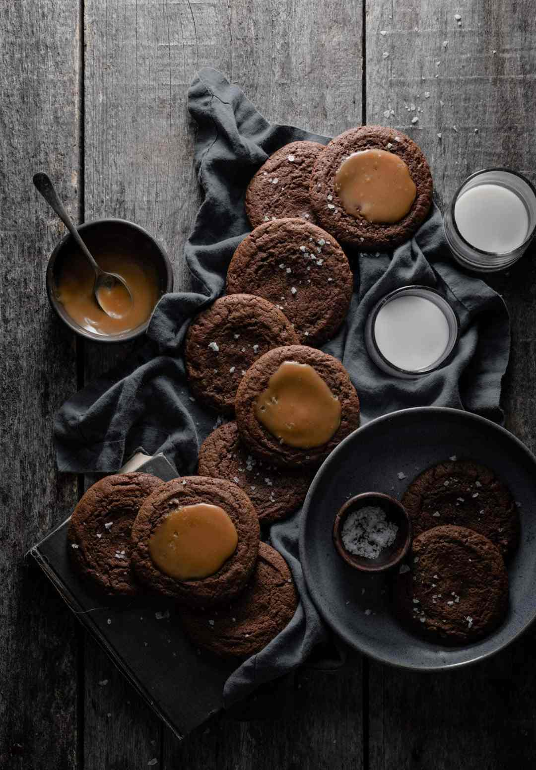 chocolate cookies topped with caramel and sea salt on wood table.