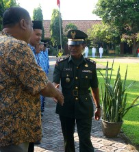 The military officer shakes hands with each teacher.