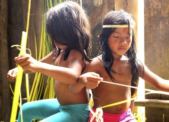Young Huaorani girls showing us how they use materials from the forest to make their goods.