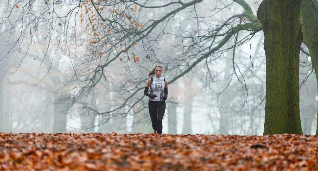 biegnąca kobieta na tle drzew i jesiennych liści