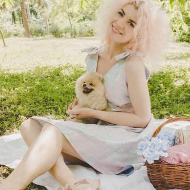 kobieta na kocu z pieskiem i koszem piknikowym