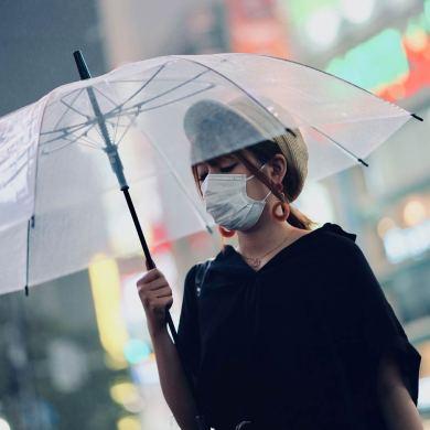 kobieta w maseczce przeciwpyłowej z przeźroczystym parasolem