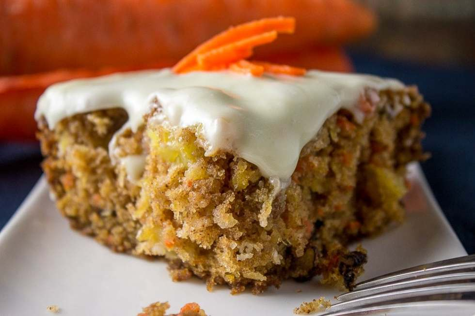 Super Moist Carrot and Pineapple Cake loaded with carrots, pineapple walnuts, and coconut and topped with a classic cream cheese icing