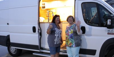 Photo: Debra and Colleen beside Colleen's Dodge Promaster camper van conversion