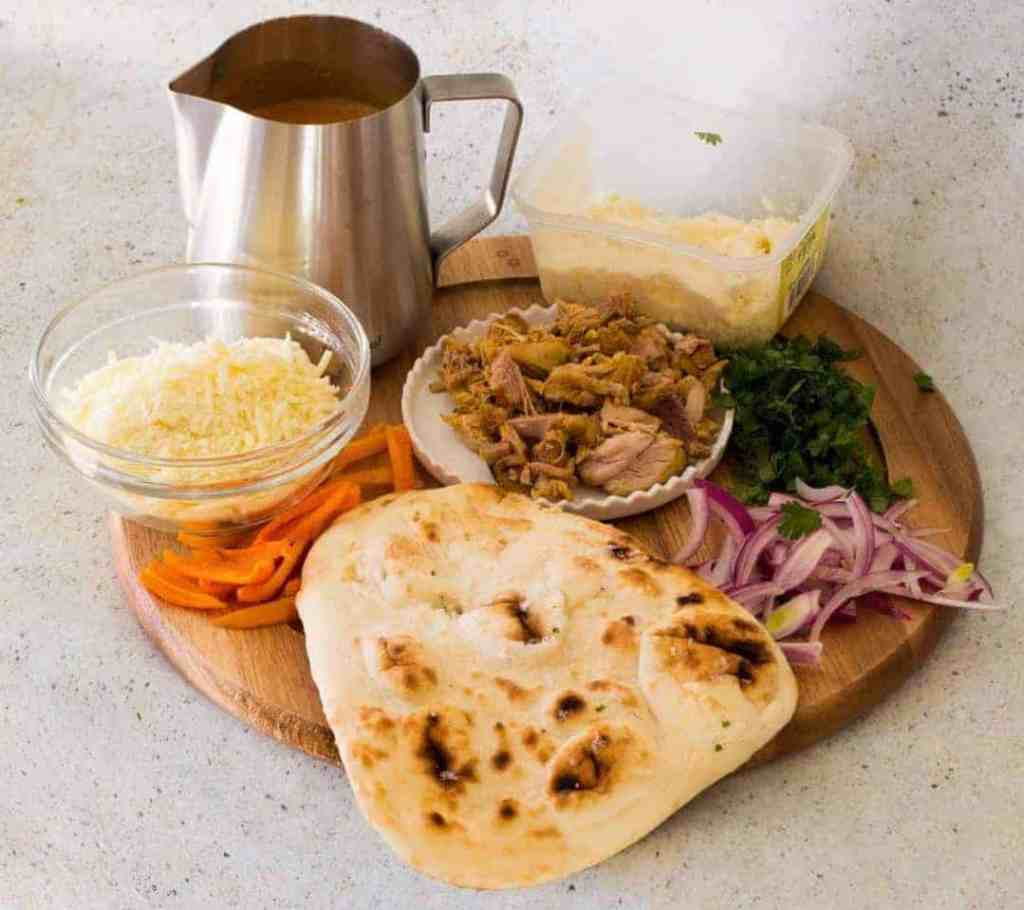 Ingredients for making butter chicken pizza on a board