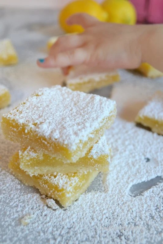 The perfect balance of sweet and tart! Mom's lemon bars combine the brightness and tartness of lemons with a shortbread-like base. Easy to make and perfect for a picnic, baby shower or Mother's day. #twosugarbugs #lemonbars #barcookies #easydessert