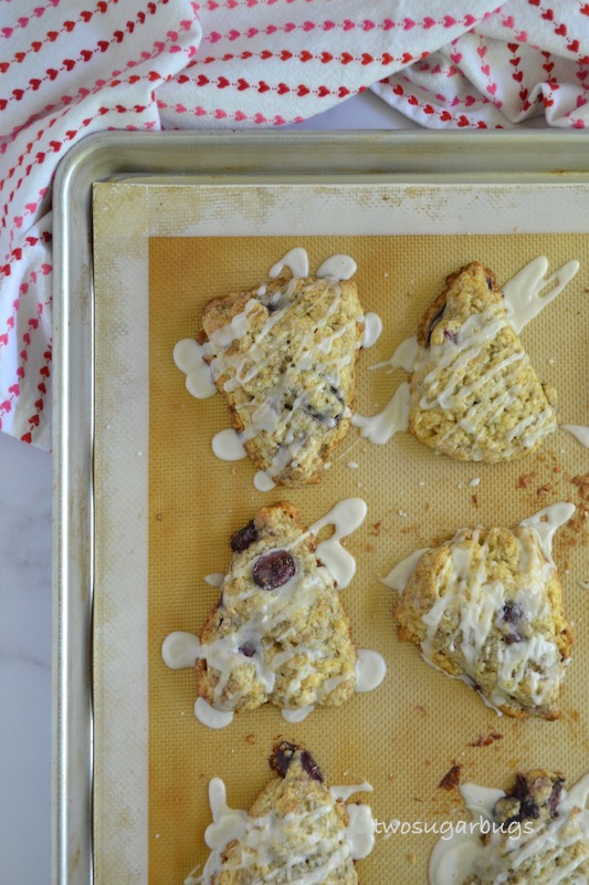 Baked and glazed cherry almond scones on the baking sheet