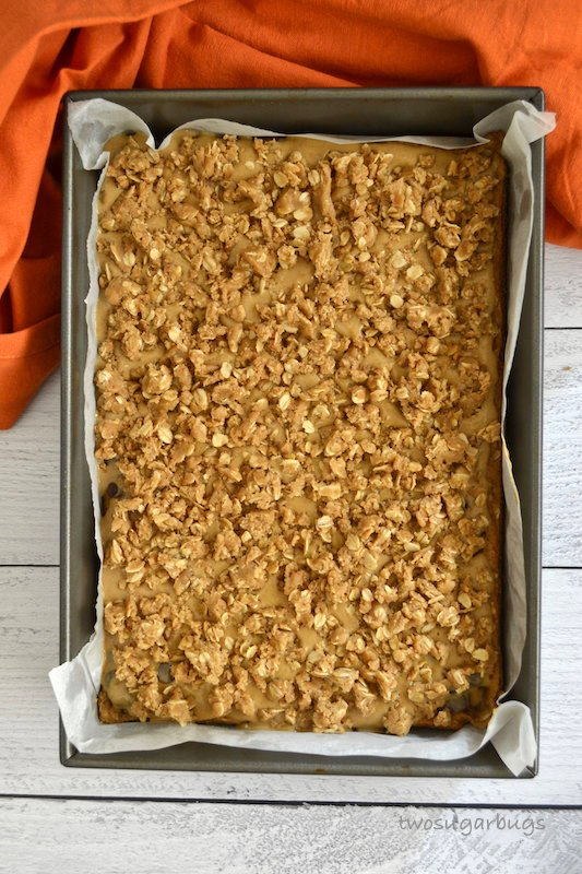 Unbaked pumpkin caramel spice bars in parchment lined pan.