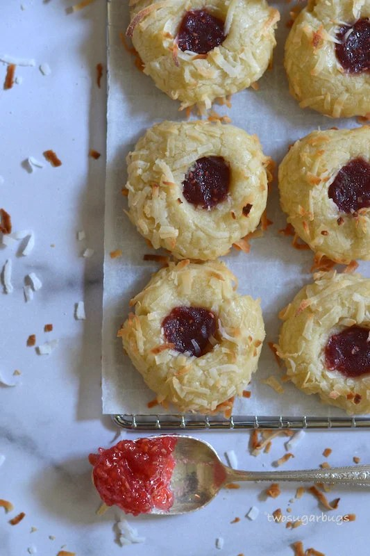 Coconut jam thumbprints on a cooling rack with a jam filled spoon