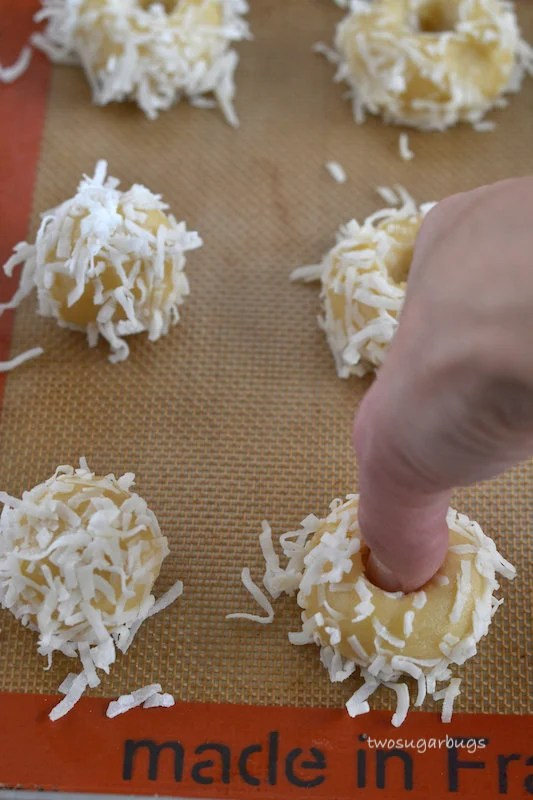 Thumb pressing indent into coconut jam thumbprint
