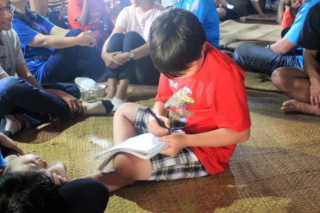 Two Worlds Treasures - signing guest book at Wae Rebo Village, Wae Rebo, East Nusa Tenggara, Indonesia.