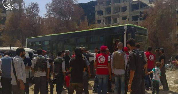 جانب من المدنيين الذين سيتم إجلاؤهم بالقرب من حافلة تتولى نقلهم (ناشطون