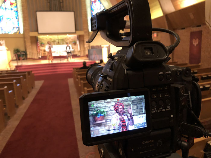 digital cinema camera filming a woman preaching in a large church